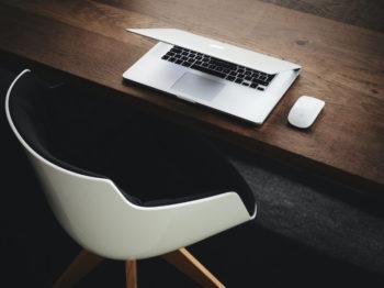 Bureau avec un ordinateur portable fermé face à une chaise