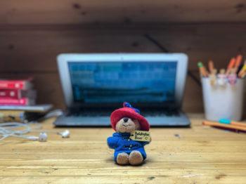 Un ours en peluche devant un ordinateur portable fermé sur une page internet