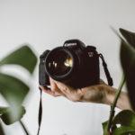 Un appareil photo tenu devant des plantes