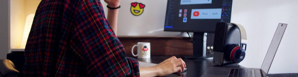 Bureau d'un graphiste en chemise à carreaux avec un ordinateur portable un ordinateur fixe et un casque