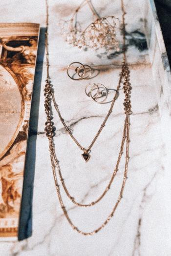 Colliers bagues et pendentifs en présentation sur un fond de marbre