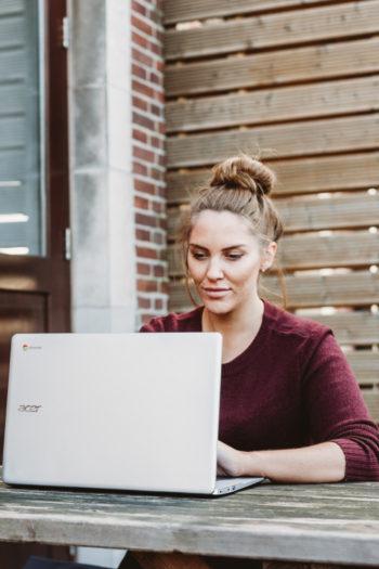Femme auto entrepreneur sur un pc portable en extérieur