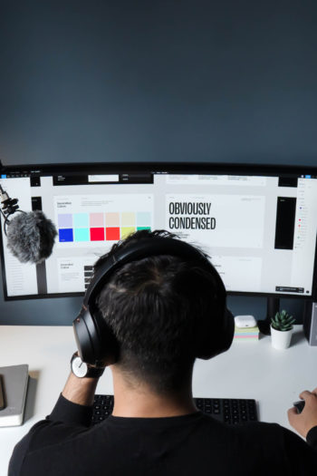 Freelance avec un casque et un micro devant un écran d'ordinateur