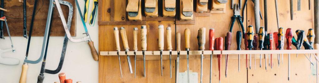 Présentoir en bois d'outils attachés sur un mur : tournevis, scies etc
