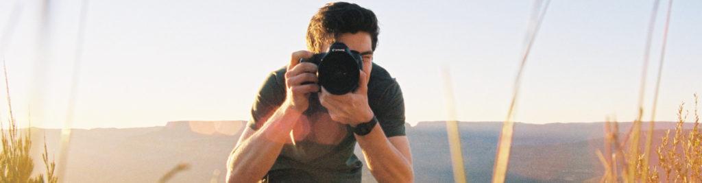 Un photographe face camera avec son appareil dans la nature