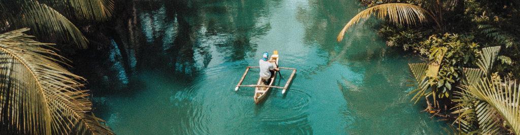Vacancier sur un canot en bois dans une rivière, décors jungle