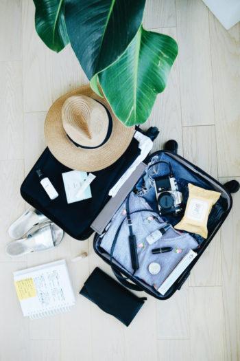 Une valise de vacancier ouverte avec un chapeau en paille