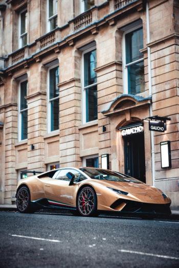 Une voiture de sport couleur or devant l'entrée d'un hôtel de luxe